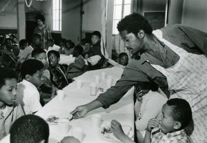 2-Charles-Bursey-hands-plate-of-food-to-a-child-seated-at-Free-Breakfast-Program.-Photo-courtesy-of-Pirkle-Jones-and-Ruth-Marion-Baruch.PJ_v1
